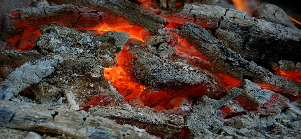Burning coal in hot campfire flame